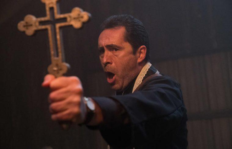 Le prêtre tenant une croix